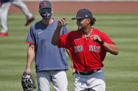 Boston Red Sox's Xander Bogaerts, right, runs past Interim Manager Ron Roenicke during baseball training camp at Fenway Park, Tuesday, July 7, 2020, in Boston. (AP Photo/Elise Amendola)