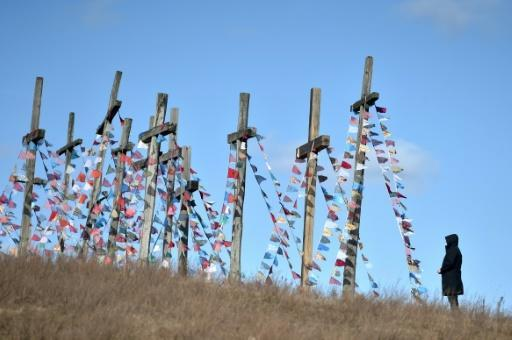A man stands in front of giant crosses in the town of Achmiany, some 130 km northwest of Minsk, during Palm Sunday celebrations