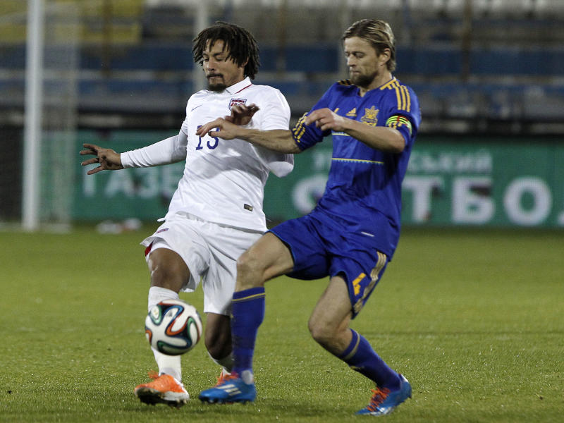 Anatroliy Tymoshchuk, right, of Ukraine fights for the ball with Jermaine Johns of U.S. during an international friendly match at Antonis Papadopoulos stadium in southern city of Larnaca, Cyprus, Wednesday, March 5, 2014. The Ukrainians are face the United States in a friendly on Wednesday in Cyprus, a match moved from Kharkiv to Larnaca for security reasons. (AP Photo/Petros Karadjias)