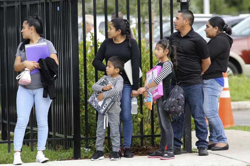 People wait in line for their appointment at the Miramar Immigration and Customs facility, Wednesday, Dec. 18, 2019, in Miramar, Fla. The children are holding toys given to them by activists and volunteers who held a holiday toy giveaway for asylum seekers, refugees and immigrants checking in at the ICE facility. (AP Photo/Lynne Sladky)