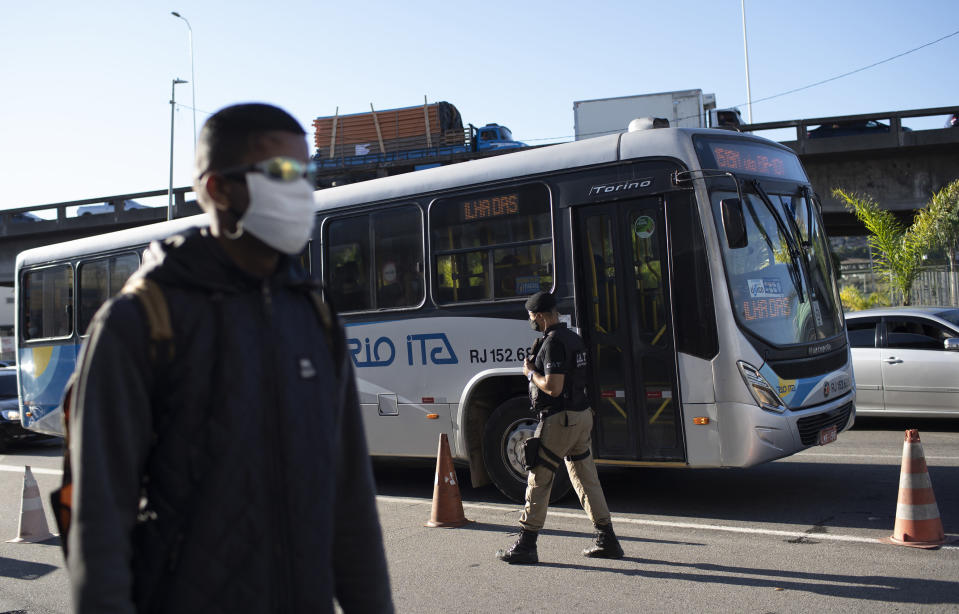A municipal police officer walks past a bus at a checkpoint to check documents and take body temperatures, amid increased restrictions on movements in an effort to curb the spread of the new coronavirus in Niteroi, Brazil, Monday, May 11, 2020. (AP Photo/Silvia Izquierdo)