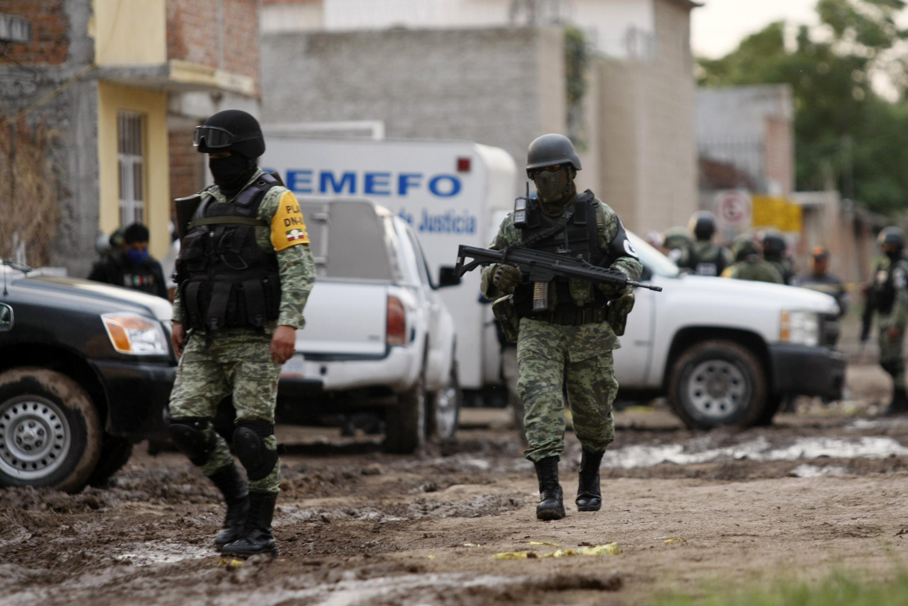 Members of the National Guard walk near the crime scene where 24 people were killed in Irapuato, Guanajuato state, Mexico, on July 1, 2020. - An armed attack at a drug rehabilitation center in Irapuato, a town in the central Mexican state of Guanajuato, left at least 24 dead and seven wounded on Wednesday, local authorities reported. (Photo by MARIO ARMAS / AFP) (Photo by MARIO ARMAS/AFP via Getty Images)