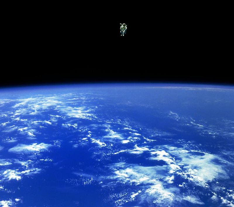"Mission Specialist Bruce McCandless II, is seen further away from the confines and safety of his ship than any previous astronaut has ever been. This space first was made possible by the Manned Manuevering Unit or MMU, a nitrogen jet propelled backpack. After a series of test maneuvers inside and above Challenger's payload bay, McCandless went ""free-flying"" to a distance of 320 feet away from the Orbiter. This stunning orbital panorama view shows McCandless out there amongst the black and blue of Earth and space. (02/12/1984)"