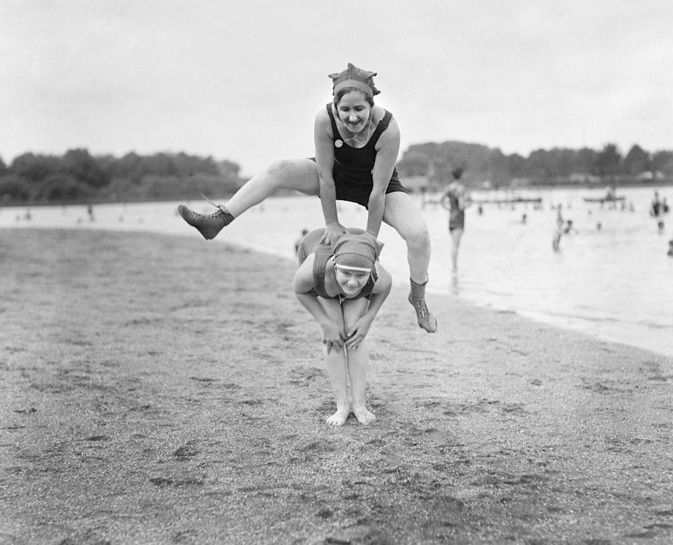 """<p>Two young women donning swim caps and bathing suits play leapfrog on the beach.</p><p>Related: <a href=""""https://www.esquire.com/lifestyle/g15897154/celebrity-beach-photos-vintage/"""" rel=""""nofollow noopener"""" target=""""_blank"""" data-ylk=""""slk:Vintage Photos of Celebrities at the Beach"""" class=""""link rapid-noclick-resp"""">Vintage Photos of Celebrities at the Beach</a></p>"""