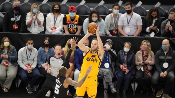 Utah Jazz forward Bojan Bogdanovic (44) shoots as San Antonio Spurs guard Dejounte Murray (5) defends while fans sit courtside in the first half during an NBA basketball game Monday, May 3, 2021, in Salt Lake City. (AP Photo/Rick Bowmer)