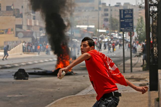 <p>A Palestinian throws stones towards Israeli security forces during clashes after a protest marking the 70th anniversary of Nakba — also known as Day of the Catastrophe in 1948 — and against the US' relocation of its embassy from Tel Aviv to Jerusalem, at the main entrance of the occupied West Bank city of Bethlehem on May 15, 2018. (Photo: Musa Al Shaer/AFP/Getty Images) </p>