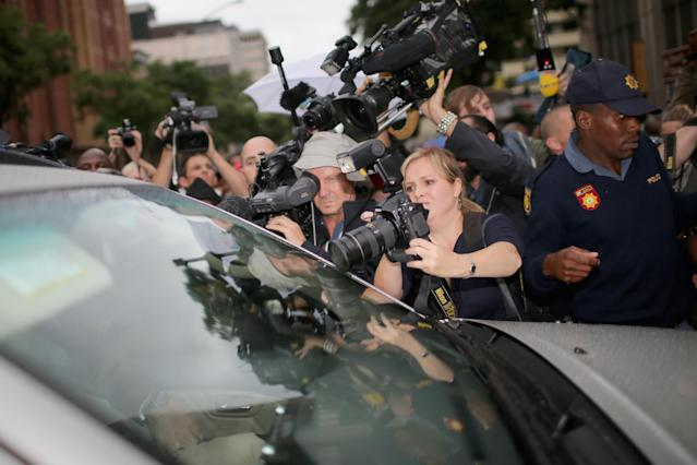 PRETORIA, SOUTH AFRICA - MARCH 03: Media and locals swarm around the car carrying Oscar Pistorius as he leaves North Gauteng High Court at the end of the first day of his trial accused of the murder of his girlfriend Reeva Steenkamp on March 3, 2014 in Pretoria, South Africa. Olympic and Paralympic athlete Oscar Pistorius, aged 27, is accused of murdering his girlfriend Reeva Steenkamp. Pistorius denies the allegation claiming he mistook Steenkamp for an intruder inside their home on Valentines Day 2013. (Photo by Christopher Furlong/Getty Images)