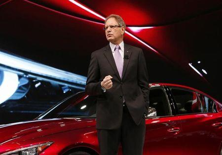 Infiniti's de Nysschen speaks next to a Q 50 Eau Rouge sedan after it was unveiled during the press preview day of the North American International Auto Show in Detroit