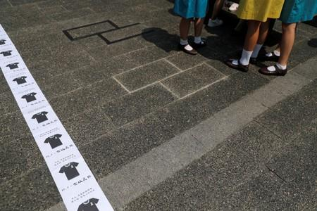FILE PHOTO: Students stand next to signs pasted on the floor calling on people to wear black as a sign of mourning on October 1, during a rally as part of a strike on the eve of China's National Day, at Chater Garden in Hong Kong