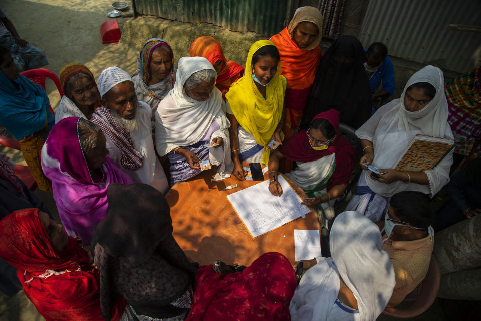 Elderly women wait to register for a COVID-19 vaccine in Bahakajari village in an interior part of Indian northeastern state of Assam, India, Tuesday, March 23, 2021. In India, workers recently trekked to the tiny village to start vaccinating its nearly 9,000 residents. (AP Photo/Anupam Nath)