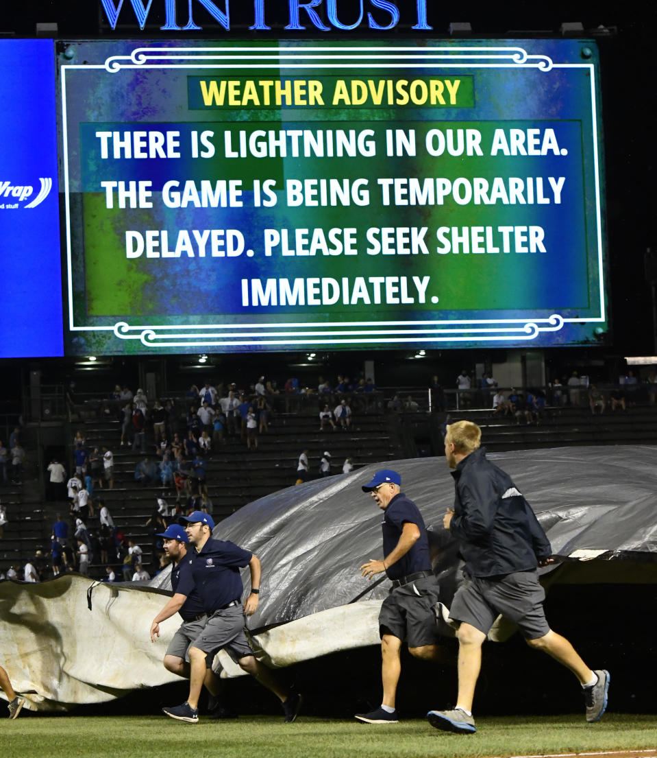 Chicago Cubs' ground crew lay down the tarp due to a storm during the 10th inning of a baseball game against the New York Mets on Tuesday, Aug. 28, 2018, in Chicago. (AP Photo/Matt Marton)