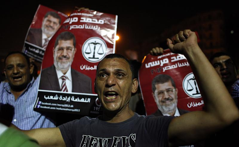 "Egyptian Muslim Brotherhood supporters chant slogans and carry posters with a picture of presidential candidate, Mohammed Morsi and Arabic that reads ""Mohammed Morsi, president for Egypt, revival is the will of the people,"" during an anti-ruling military council demonstration in Tahrir Square, Cairo, Egypt Wednesday, June 20, 2012. Authorities delayed Thursday's planned announcement of the winner of Egypt's presidential election, likely for several days, hiking tension as allegations of fraud swirled and each candidate declared he was the victor. (AP Photo/Nasser Nasser)"