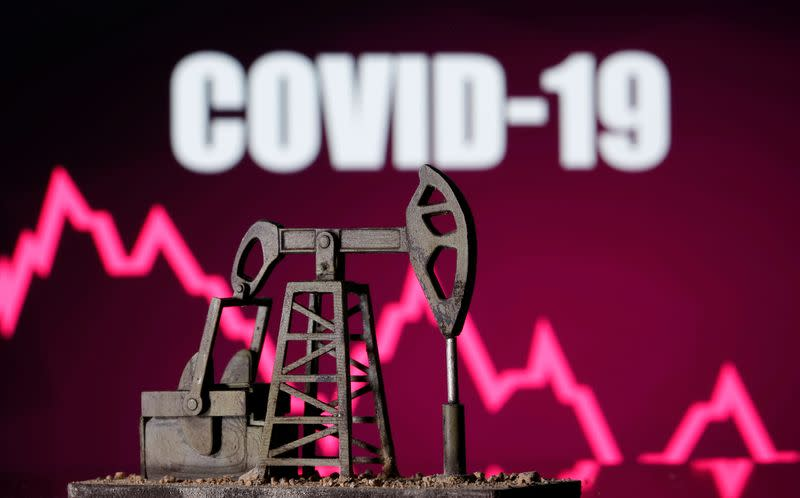 "FILE PHOTO: A 3d printed oil pump jack is seen in front of displayed stock graph and ""COVID-19"" words in this illustration picture"