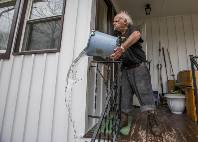 <p>Robert Forler tosses a bucket out water off his front porch as he tries to clear standing water from his home on Emerson Avenue Wednesday, Feb. 21, 2018, in South Bend, Ind. (Photo: Robert Franklin/South Bend Tribune via AP) </p>