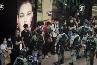 Police check pedestrians during China's National Day in Causeway Bay, Hong Kong, Thursday, Oct. 1, 2020. A popular shopping district in Causeway Bay saw a heavy police presence after online calls urged people to join protests. (AP Photo/Kin Cheung)