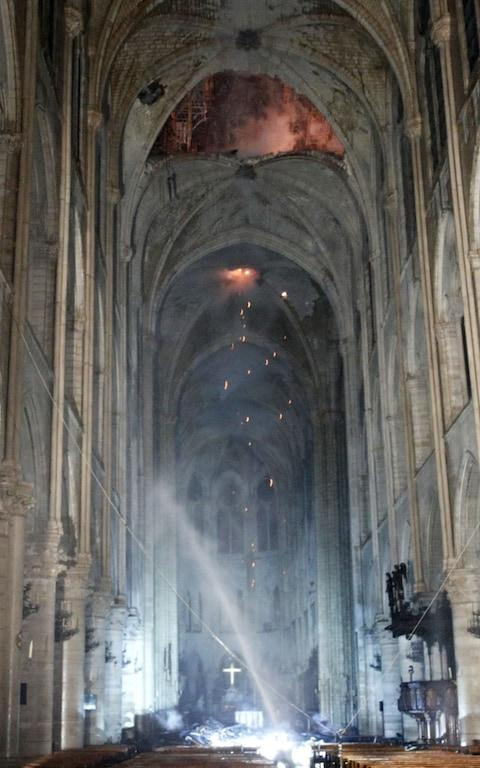 General view of the interior of the Notre-Dame Cathedral as flames burn the roof - Credit: Rex