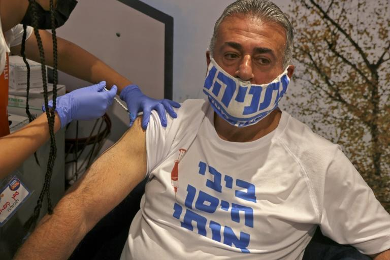 An Israeli man wearing a shirt that reads 'Bibi (Prime Minister Benjamin Netanyahu) vaccinated me' is inoculated in Jerusalem