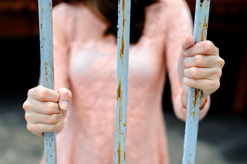 Close up thin focus on young woman hand in pink dress hole on rust iron bark in dark tone color