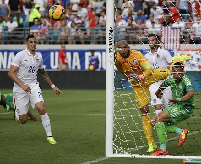 United States goalkeeper Tim Howard (1) deflects a ball away from the goal as he collide with Nigeria's Peter Odemwingie (8) as United States's Geoff Cameron (20) and Kyle Beckerman (15) come in to help during the first half of an international friendly soccer match in Jacksonville, Fla., Saturday, June 7, 2014. (AP Photo/John Raoux)