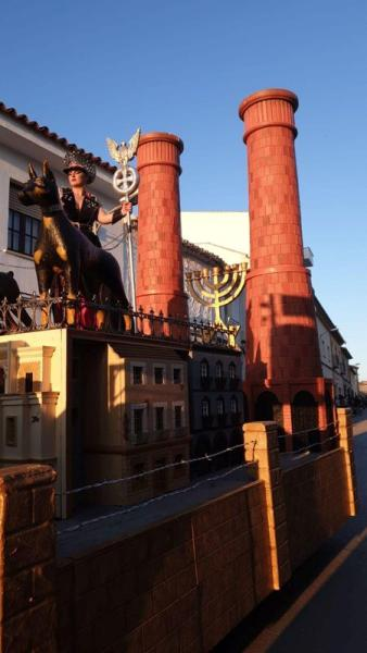 A woman is seen standing on a carnival float depicting Third Reich eagle symbol, Menorah candle holder and crematorium chimneys, during a carnival parade in Campo de Criptana