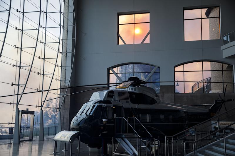 Marine One stands on display in the Ronald Reagan Presidential Library as smoke rises outside during the Easy Fire in Simi Valley, Calif. on Oct. 30, 2019.  (Photo: Patrick T. Fallon/Bloomberg via Getty Images)