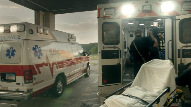 Two paramedics in the back of an ambulance, adjacent to an empty stretcher, with another ambulance parked alongside.