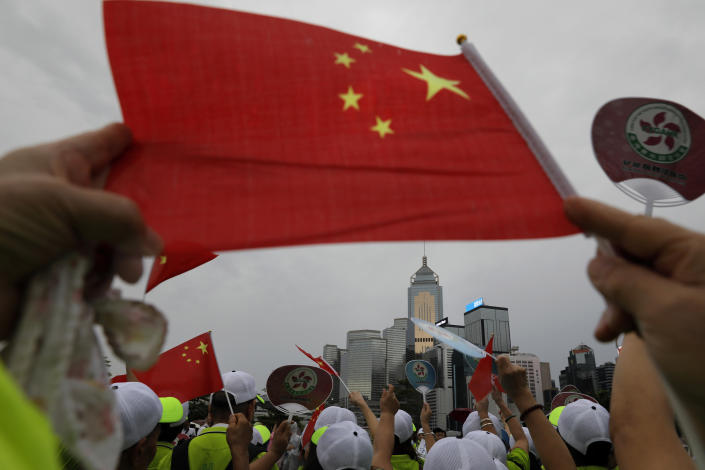Pro-China supporters wave a Chinese national flag to support police and anti-violence during a rally in Hong Kong Saturday, Aug. 17, 2019. Another weekend of protests is underway in Hong Kong as Mainland Chinese police are holding drills in nearby Shenzhen, prompting speculation they could be sent in to suppress the protests. (AP Photo/Vincent Yu)