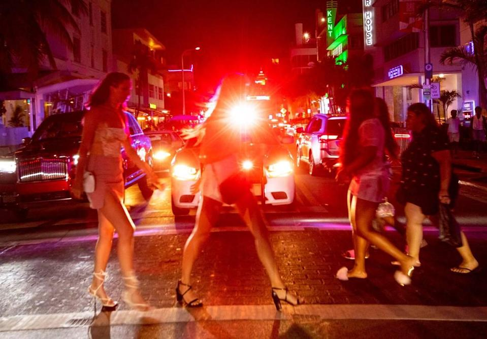 People cross Collins Avenue after curfew in Miami Beach, Florida, on Saturday, March 27, 2021.