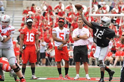 J.T. Barrett (16) and Braxton Miller (5) look on while Cardale Jones takes reps at QB during spring practice. (Getty)