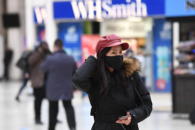A woman wearing a face mask on her phone at Victoria Station in London.