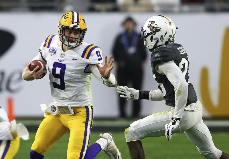LSU quarterback Joe Burrow (9) tries to elude UCF defensive back Kyle Gibson (25) during the first half of a Fiesta Bowl NCAA college football game Tuesday, Jan. 1, 2019, in Glendale, Ariz. (AP Photo/Ross D. Franklin)