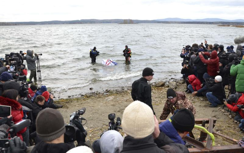 Divers stand in the waters of the Chebarkul Lake during the demonstration of the lifting of an object, which is a piece of a meteorite according to local authorities and scientists, some 80 kilometers (50 miles) west of Chelyabinsk October 16, 2013. The meteorite exploded over central Russia in February 2013, raining fireballs over a vast area and causing a shock wave that smashed windows, damaged buildings and injured more than 1,000 people, according to local media. REUTERS/Anton Melnikov (RUSSIA - Tags: DISASTER SCIENCE TECHNOLOGY ENVIRONMENT)