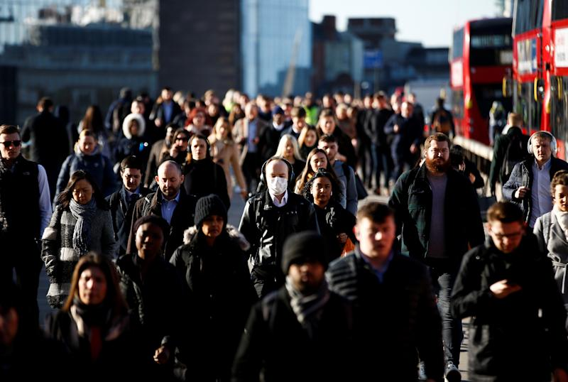 People, some wearing protective face masks, walk over London Bridge, as the number of coronavirus cases worldwide continues to grow, in London, Britain, March 16, 2020. REUTERS/Henry Nicholls