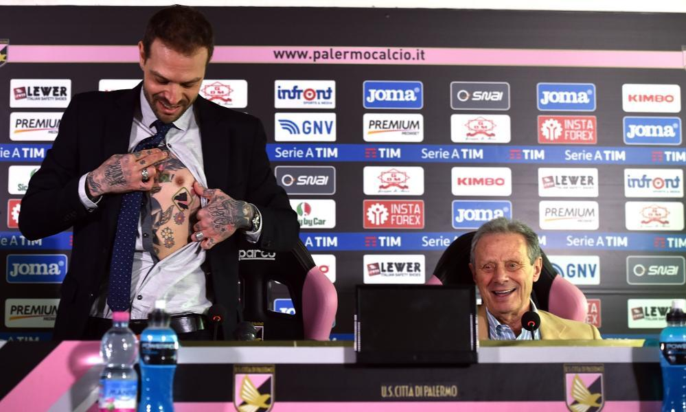 Paul Baccaglini (L) new President of Palermo shows a tattoo displaying a club logo as former president Maurizio Zamparini looks on.
