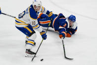 New York Islanders' Adam Pelech (3) fights for control of the puck with Buffalo Sabres' Henri Jokiharju (10) during the second period of an NHL hockey game Thursday, March 4, 2021, in Uniondale, N.Y. (AP Photo/Frank Franklin II)