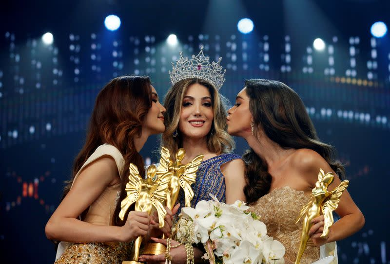 Thailand's Ruethaipreeya Nuanglee and Brazil's Ariella Moura kiss Mexico's Valentina Fluchaire after she won crown at the final show of the Miss International Queen 2020 transgender beauty pageant in Pattaya