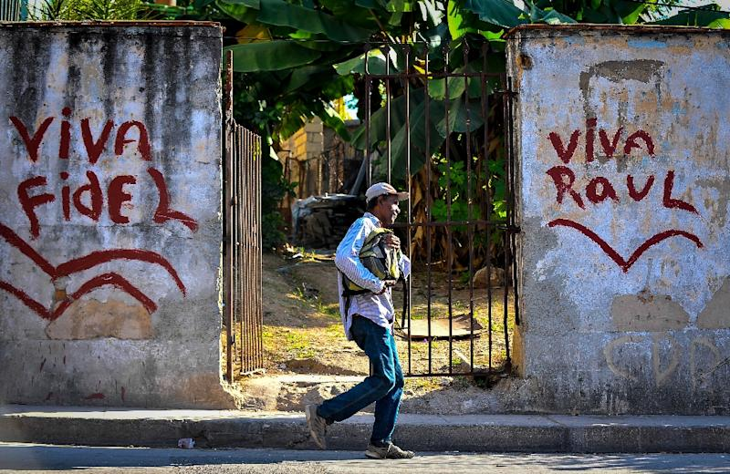 """A man walks next to graffitis reading """"Long live Fidel"""" and """"Long live Raul"""" in a street of Havana, on November 27, 2016 (AFP Photo/Yamil Lage)"""
