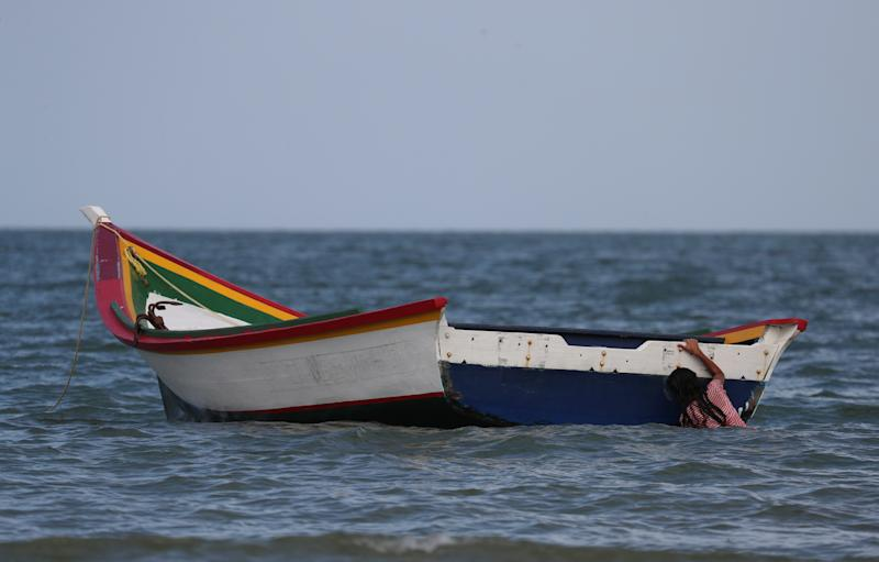 A girl holds on to a boat while playing near where Maroly Bastardo disappeared in the Caribbean Sea, in Guiria, Venezuela, on May 24. (Photo: Ivan Alvarado/Reuters)