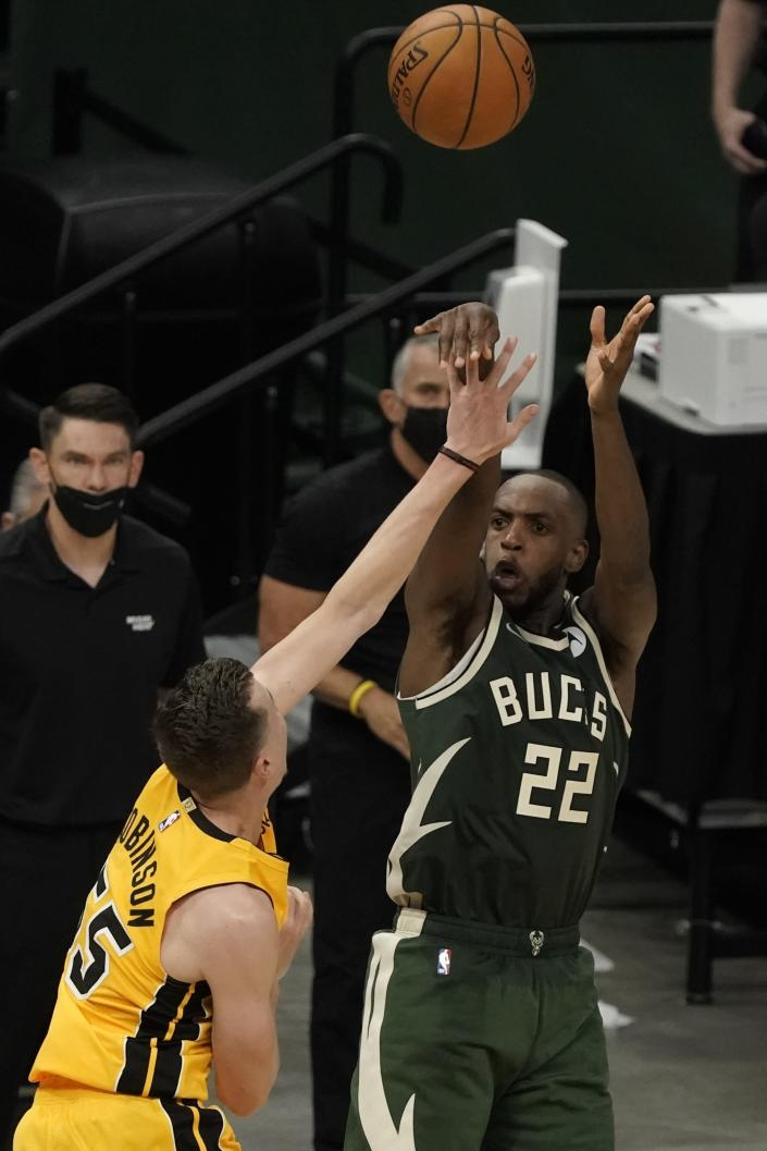 Milwaukee Bucks' Khris Middleton makes a basket over Miami Heat's Duncan Robinson in the final seconds of overtime of Game 1 of their NBA basketball first-round playoff seriesSaturday, May 22, 2021, in Milwaukee. The Bucks won 109-107 to take a 1-0 lead in the series. (AP Photo/Morry Gash)