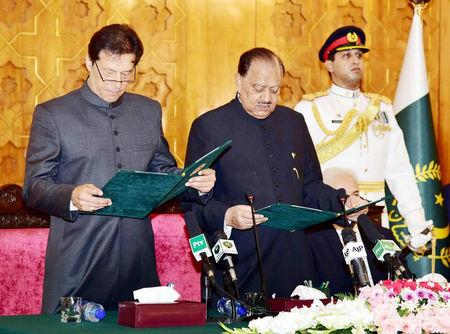 Cricketer-turned-politician Imran Khan takes the oath of the Prime Minister from President Mamnoon Hussain at the Presid House in Islamabad