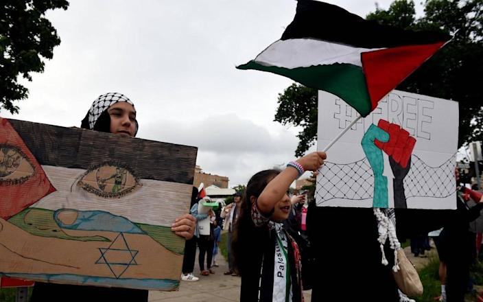Rama Allen, 13, left, and her sister, Yasmin, 7, joined about 250 others Saturday evening at Mill Creek Park on the Country Club Plaza for a pro-Palestinian rally condemning the Israeli occupation of Palestine and the violation of human rights. Protestors called for an end to violence against Palestinians, the displacement of families from the East Jerusalem neighborhoods of Sheikh Jarrah and Silwan, the desecration of the Al-Aqsa mosque, and the recent military attacks on civilian populations in Gaza and throughout greater Palestine.