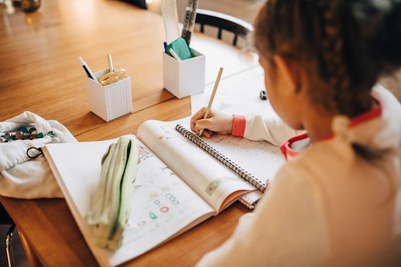 Rear view of girl writing homework on table while sitting at home