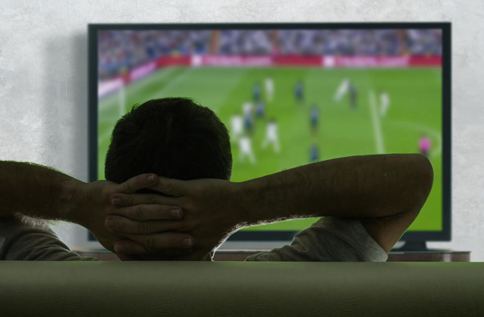 view from behind of young and happy soccer fan man watching European football game on big screen television at living room sofa couch enjoying and feeling the emotion cheering his team