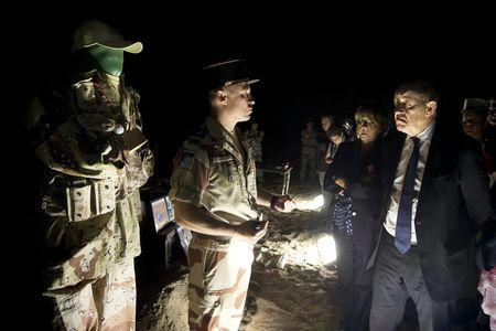 French Defence Minister Jean-Yves Le Drian speaks with soldiers of the 13th Demi-Brigade of the Foreign Legion, during a visit to the military base of the Foreign Legion, in the United Arab Emirates