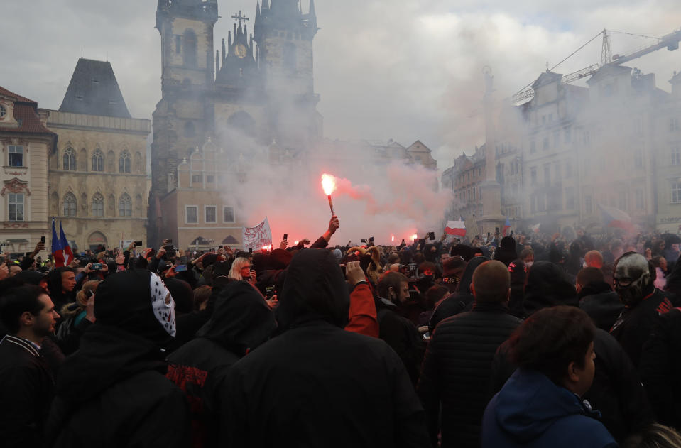 Protesters light up flares at the Old Town Square in Prague, Czech Republic, Sunday, Oct. 18, 2020. Czech police used tear gas and a water cannon to disperse crowd of hundreds of violent protesters who attacked them after a rally in Prague against the government's restrictive measures imposed to slow the spread of the coronavirus infections. (AP Photo/Petr David Josek)