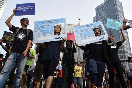 Activists hold placards in the shape of national identity cards (KTP) during a protest calling for the investigation into alleged corruption linked to the procurement of the electronic cards by government officials in Jakarta