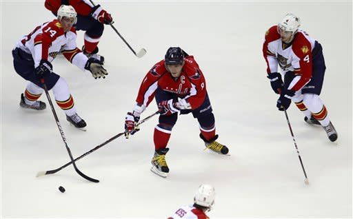 Washington Capitals left wing Alex Ovechkin (8), of Russia, maneuvers the puck between Florida Panthers left wing Tomas Fleischmann (14), of the Czech Republic, defenseman Keaton Ellerby (4) and center Stephen Weiss, bottom, during the second period of an NHL hockey game Tuesday, Feb. 7, 2012, in Washington. (AP Photo/Haraz N. Ghanbari)