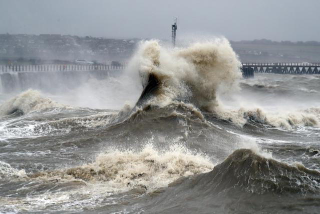 Waves crash into the wall at Newhaven in East Sussex. (PA)
