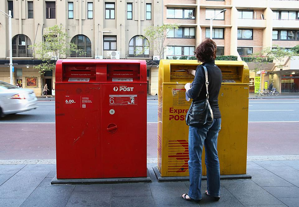 Image of Australia Post boxes with a lady standing in front of it