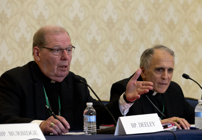 Robert Deeley, left, Bishop of the Diocese of Portland, accompanied by Cardinal Daniel DiNardo, of the Archdiocese of Galveston-Houston and President of the United States Conference of Catholic Bishops (USCCB), speaks during a news conference at the United States Conference of Catholic Bishops (USCCB), 2019 Spring meetings in Baltimore, Md., Tuesday, Jun 11, 2019. (AP Photo/Jose Luis Magana)